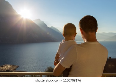 Rear view at father holding kid son or daughter looking at mountains and sea view sunrise, dad and his baby enjoying sunny beautiful morning travelling together, daddy and child relaxing on vacation