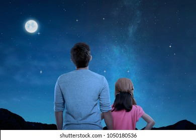 Rear view of father and little daughter looking at night scene at outdoor