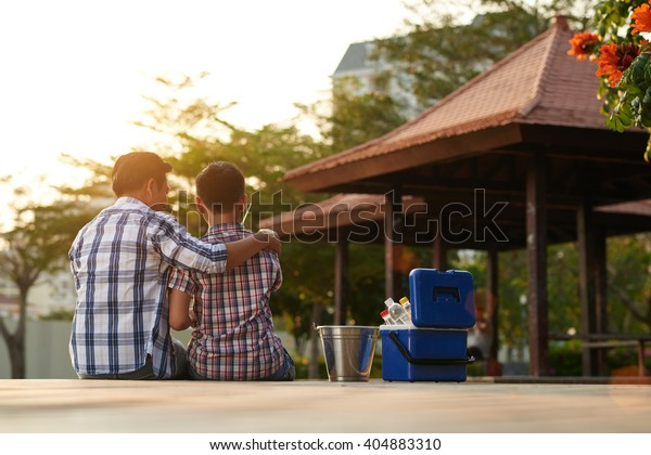 Rear view of father and son spending time fishing in the park