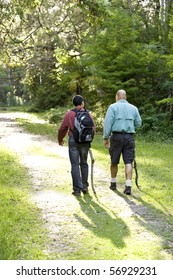Rear view father and teenage son hiking on path in woods
