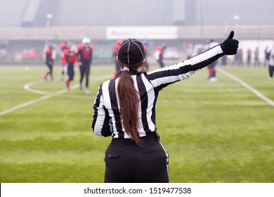 rear view of female american football referee giving signals to professional players during match on the stadium field