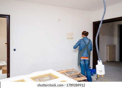 Rear view of female architect woman testing light paint on the renovated wide room wall during the general reconstruction of her dream house