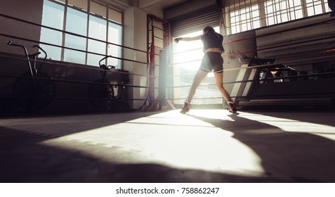 Rear view of female boxer doing shadow boxing inside a boxing ring. Boxer practicing her punches at a boxing studio.