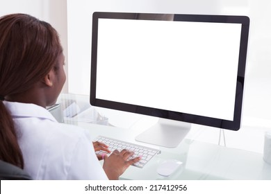 Rear view of female dentist using desktop PC in clinic