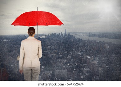 Rear view of female executive carrying red umbrella against new york
