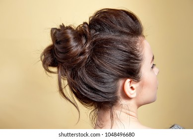 Rear view of female hairstyle middle bun with brown hair.