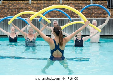 Rear view of female Instructor and senior swimmers exercising with pool noodle