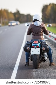 Rear view at female motorcyclist with motorcycle resting on the roadside of a country highway