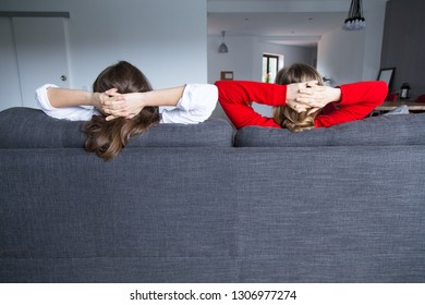 Rear view of female roommates relaxing on couch in living room. Back view of young lesbian couple enjoying weekend at home. Real estate concept