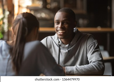 Rear view female sitting in cafe public place focus on cheerful african male, interracial millennial people participating in speed dating search soul mate, multiracial relationships and love concept