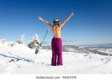 Rear view of female skier posing topless on mountain slope