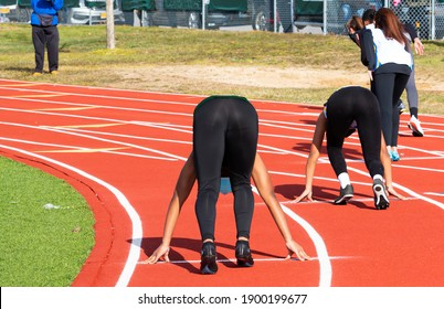 Rear view of female sprinter runners in the set position on on outdoor track during a high school track and field meet wearing spandex.