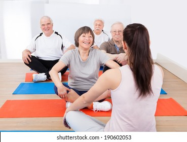 Rear view of female trainer training senior customers on floor in yoga class