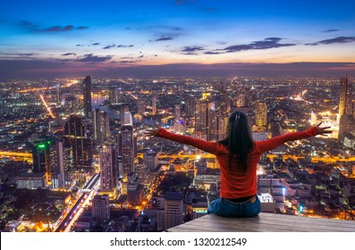 Rear view of female traveler with raised hands standing on the top of a tower and looking at the  urban city with sunset sky. Woman happy enjoying the city view from top of a city at twilight.