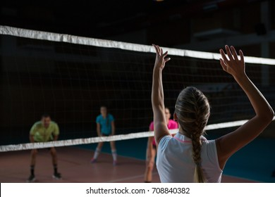 Rear view of female volleyball player with arms raised playing at court
