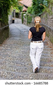 Rear view of a female walking down stairs in a romantic italian city