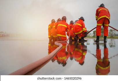 Rear view of Firefighters group demonstration extinguish a fire during training in industry plant with sunlight. Fire in the industrial Factory, Rescue Teamwork concept.