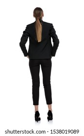 rear view of a fit businesswoman wearing black suit standing with hands in pockets against white studio background