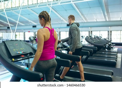 Rear view of fit Caucasian male and female athletic exercising on treadmill in fitness center. Bright modern gym with fit healthy people working out and training