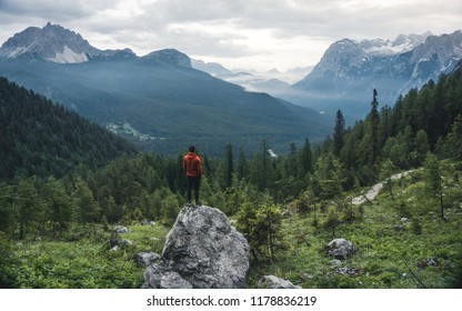 Rear view of the fit man resting on rock at beautiful sunrise. Beautiful landscape with forest landscape. Healthy and active lifestyle. Italy Dolomites