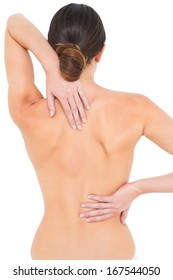 Rear view of a fit topless young woman with back pain standing over white background