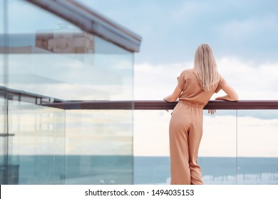 Rear view of fit unidentified young woman tourist admiring magnificent view from hotel terrace to the sea and the horizon. Beautiful woman admires the view after the long-awaited arrival on vacation