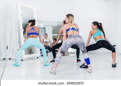 Rear view of fit young girls practicing twerk movements in dancing workshop