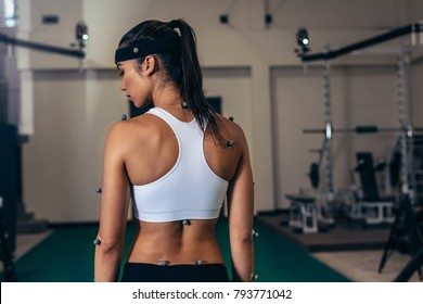 Rear view of fit young woman with motion capture sensors on her body at sports science lab. Biomechanics lab with female athlete testing her performance.