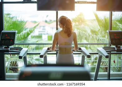 Rear view of fitness woman exercising with listening music and running on treadmill machine in gym in blurred background front of against big window,concept for exercising