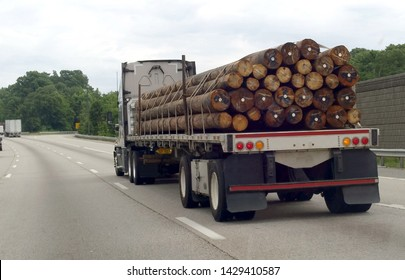 Rear view of flatbed semi truck hauling a cargo of telephone poles.