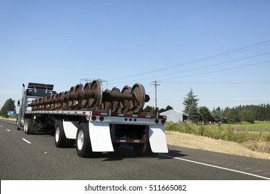 Rear view of flatbed truck hauling cargo of railroad train wheels.