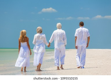Rear view of four people, two seniors, couples or family generations, holding hands, walking on an empty tropical beach