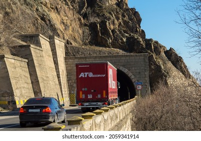Rear view of freight truck on the mountain road, at the entrance to the tunnel. Truck belonging to the Slovak company ATO TRANS. Import and export of goods concept. Orsova, Romania, October 15, 2021