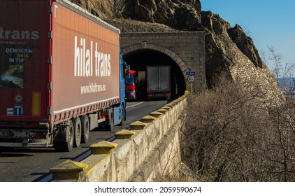 """Rear view of freight trucks on the  mountain road, at the entrance or exit of the tunnel. Truck belongs to the Turkish company """"Hilal Trans"""". Severin, October 17, 2021."""