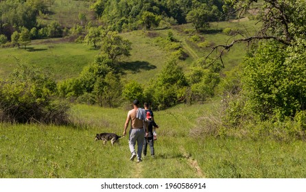 Rear view of friends walking on the green hill on a sunny spring day. Country road landscape with few people in walk. Vatra Dornei, Maramures, Romania, May 23, 2020
