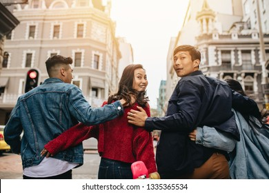 Rear view of friends walking together outdoors with arms around, with couple looking back. Group of asian men and women hanging out.