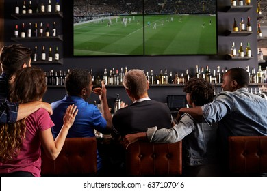 Rear View Of Friends Watching Screen In Bar Together
