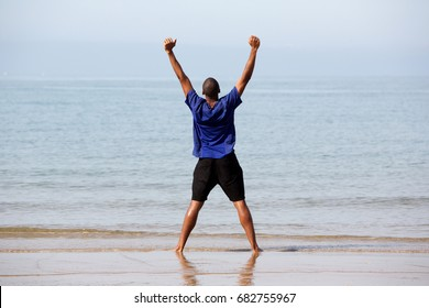 Rear view full body portrait of excited young man standing on beach with arms outstretched