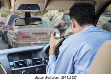 Rear view of furious young man driving a car on the road at the traffic jam