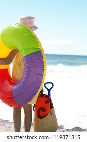 Rear view of a girl carrying a large colourful inflated plastic beach ring over her shoulder on the sandy beach
