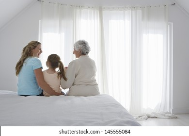 Rear view of girl with grandmother and mother sitting together on bed
