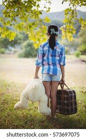 Rear view of a girl standing in the park with a teddy bear and suitcases