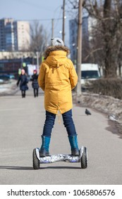 Rear view at girl in yellow jacket driving on self-balanced gyroscooter on urban streets