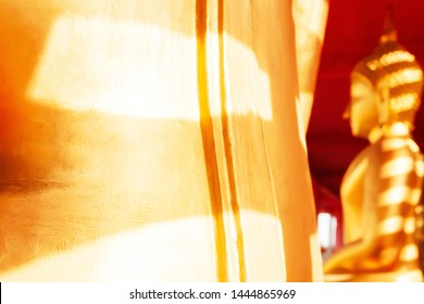 Rear view of golden Buddha images with a striped shadow from the buddhist temple. Selective focus.