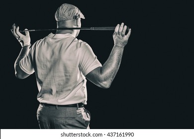 Rear view of golf player holding a golf club against black background