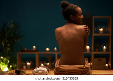 Rear view of gorgeous naked woman sitting on the massage bed after having spa procedure