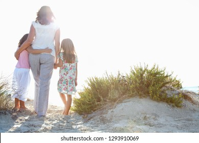 Rear view of grand mother senior female and grand daughters children standing on beach dunes contemplating the ocean with flare sunny sky, nature outdoors, bonding activities family lifestyle.