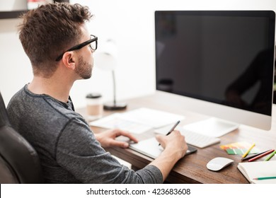 Rear view of a graphic designer using a pen tablet in front of a computer in an office. Blank computer screen