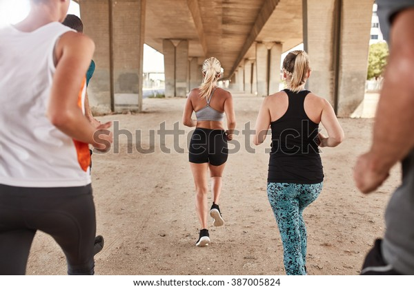 Rear view of group of athletes running under a bridge. Runners training together.