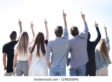rear view. a group of business youth pointing up at a copy space
